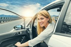 Beautiful blonde girl driving a car on the highway. Invitation to travel. Car rental or vacation. Beautiful blonde girl driving a car on the highway. The woman Royalty Free Stock Photos