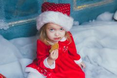 Beautiful blonde girl eating cookie in Santa Claus costume. Beautiful little girl with cookies for Santa Claus in festively decorated room Stock Photography