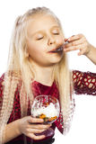 Beautiful blonde girl eating dessert. Isolated over white background stock photography
