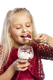 Beautiful blonde girl eating dessert. Isolated over white background royalty free stock photography