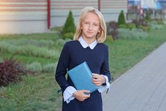 Beautiful blonde girl in elegant dress with book in hands near school. Schoolgirl likes to learn and read royalty free stock photography