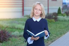 Beautiful blonde girl in elegant dress with book in hands near school. Schoolgirl likes to learn and read royalty free stock photos