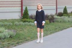 Beautiful blonde girl in elegant dress goes to school. Back to school stock image