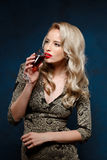 Beautiful blonde girl in evening dress drinking wine at party. Stock Photo