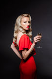 Beautiful blonde girl in evening dress posing, holding champaign glass. Young beautiful blonde girl in red evening dress holding champaign glass, looking at Royalty Free Stock Photography
