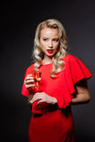 Beautiful blonde girl in evening dress posing, holding champaign glass. Young beautiful blonde girl in red evening dress holding champaign glass at party over Royalty Free Stock Photo