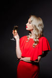 Beautiful blonde girl in evening dress posing, holding champaign glass. Stock Images