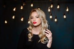 Beautiful blonde girl in evening dress posing, holding wine glass. Stock Image