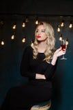 Beautiful blonde girl in evening dress posing, holding wine glass. Stock Photos
