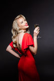 Beautiful blonde girl in evening dress smiling, holding champaign glass. Royalty Free Stock Photography
