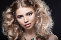 Beautiful blonde girl with evening make-up and unusual hairstyle with braids. Beauty face. Royalty Free Stock Image