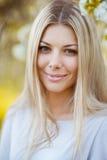 Beautiful blonde girl face in spring garden Stock Photos