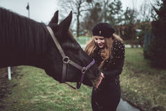 Beautiful blonde girl feeds from a hand a big brown horse Royalty Free Stock Photography