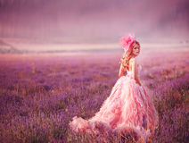 Beautiful blonde girl in a field of lavender. Beautiful woman is wearing magic purple fashion dress posing at field of purple lavender flowers stock photo
