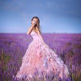 Beautiful blonde girl in a field of lavender. Beautiful woman is wearing magic purple fashion dress posing at field of purple lavender flowers royalty free stock photography