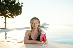 Beautiful Blonde girl with fresh juice in luxury pool Royalty Free Stock Photography