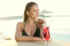 Beautiful Blonde girl with fresh juice in luxury pool Royalty Free Stock Images
