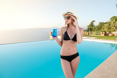 Beautiful Blonde girl with fresh juice standing by the luxury pool Royalty Free Stock Photos