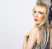 Beautiful blonde girl in fur hat on grey background Royalty Free Stock Photos