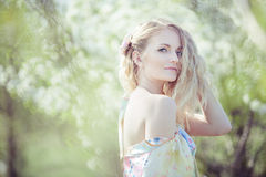 Beautiful blonde girl in the garden on a sunny day Stock Photos