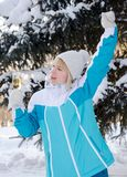 Beautiful blonde girl with a glass of champagne sings and dances. Outdoors on a background of snowy fir-trees in winter royalty free stock photos