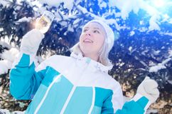 Beautiful blonde girl with a glass of champagne sings and dances outdoors on a background of snowy fir-trees in winter stock photos