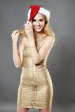 Beautiful blonde girl in a gold dress and hat ready for Christma Stock Images