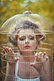 Beautiful blonde girl in a golden cage Royalty Free Stock Photo