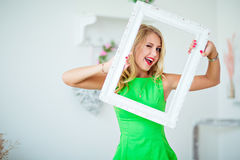Beautiful blonde girl in a green dress holding frame and winks Royalty Free Stock Images