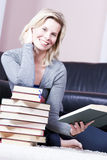 Beautiful blonde girl happily reading. Royalty Free Stock Image