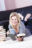 Beautiful blonde girl happily reading. Royalty Free Stock Photos