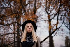 Beautiful blonde girl in a hat and black shawl standing in autumn park full of yellow leaves stock image