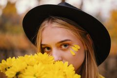 Beautiful blonde girl in a hat with bouquet of yellow flowers in autumn park full of yellow leaves royalty free stock photo