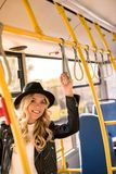 Beautiful blonde girl in hat and leather jacket smiling at camera. In bus Stock Photo