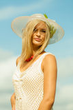Beautiful blonde girl in hat on sky background. Fashion, happiness and lifestyle concept. Portrait of lovely blonde girl in summer hat wearing white lace dress Royalty Free Stock Photo