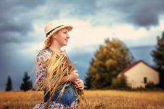 Beautiful blonde girl in hat in wheat field.