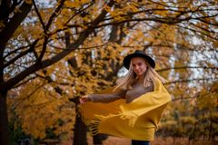 Beautiful blonde girl in a hat and yellow shawl dancing in autumn park full of yellow leaves stock images