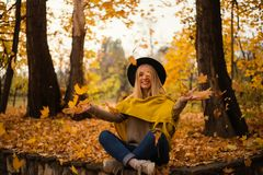 Beautiful blonde girl in a hat and yellow shawl having fun and laughing in autumn park full of yellow leaves royalty free stock photography