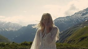Beautiful blonde girl having fun on the top of the world, smiling to camera. stock video footage