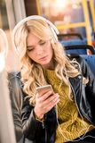 Beautiful blonde girl in headphones using smartphone. In public transport Stock Images