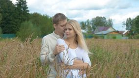 A beautiful blonde girl and her boyfriend are hugging on a wheat field. The guy hugs his girlfriend and gently pats her on the shoulder. She smiles happily and stock footage