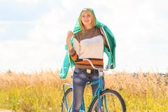 Beautiful blonde girl at her cycling on dirt road Stock Photography