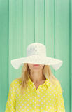 Beautiful blonde girl hiding behind hats fields. Space for text Royalty Free Stock Images