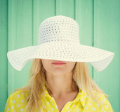 Beautiful blonde girl hiding behind hats fields. Space for text Royalty Free Stock Photo