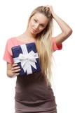 Blonde girl holding gift box. Beautiful blonde girl holding gift box, looking at camera Stock Images