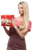 Blonde girl holding gift box. Beautiful blonde girl holding red gift box, looking at camera Royalty Free Stock Photography
