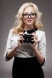 Blonde girl with camera wearing eyeglasses Royalty Free Stock Photo