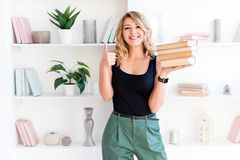 Beautiful blonde girl holding a stack of books and showing thumbs up. The concept of education, courses, examinations. Homework, list of books to read stock images