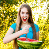 Beautiful blonde girl holds a half of watermelon. Beautiful blonde girl in a blue dress with long hair holds a half of watermelon with knife Royalty Free Stock Photos