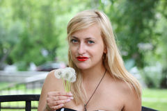 Beautiful blonde girl holds some dandelions Royalty Free Stock Image